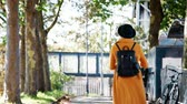 três pessoas : Back view of a fashionable young woman wearing a black hat and a yellow coat walking along a treelined street carrying a rucksack on sunny day, close up