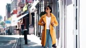 três pessoas : Fashionable young black woman wearing blue jeans and an unbuttoned yellow pea coat walking on pavement near shops on a sunny day smiling, close up
