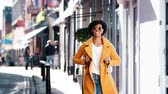 três pessoas : Fashionable young black woman wearing blue jeans and an unbuttoned yellow pea coat walking on a street past shops on a sunny day, smiling, close up