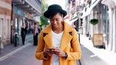 ervilha : Millennial black woman wearing a yellow pea coat and a homburg hat using her smartphone standing on a street and walking out of shot, close up