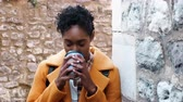 髪型 : Millennial black woman wearing a yellow coat leaning on a stone wall in an alleyway drinking a takeaway coffee, close up