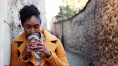 плед : Millennial black woman wearing a yellow coat leaning on a stone wall in an alleyway drinking a takeaway coffee, focus on foreground Стоковые видеозаписи