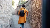ervilha : Back view of young black woman wearing a yellow pea coat putting smartphone in the back pocket of her jeans and walking away from camera down a narrow alleyway between stone walls, selective focus Stock Footage