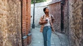 três pessoas : Young woman wearing a plaid shirt and blue jeans walking towards camera in an alley between old stone walls holding a takeaway coffee, selective focus