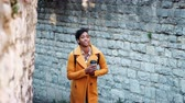 cabelo curto : Millennial black woman wearing a yellow pea coat walking in an alleyway in a historical district holding a takeaway coffee, selective focus Stock Footage