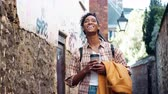 foco no primeiro plano : Young black woman wearing a plaid shirt standing in an alleyway holding her coat and a takeaway coffee, smiling to camera, close up