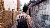 foco no primeiro plano : Young black woman with a backpack walking in a narrow alleyway between stone walls, back view, follow shot Vídeos