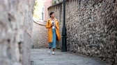 плед : Young black woman wearing an unbuttoned yellow pea coat and jeans walking in an alley in historical district listening to music and holding a takeaway coffee, low angle Стоковые видеозаписи