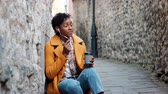 três pessoas : Young woman wearing a yellow pea coat and blue jeans sitting in an alleyway in a historical city talking on her smartphone using earphones, close up