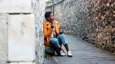 髪型 : Young woman wearing a yellow pea coat and blue jeans sitting in an alleyway in a historical city talking on her smartphone using earphones, full length, selective focus 動画素材
