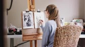 portrait shot : View through doorway as female teenage artist draws outline for portrait of pet dog in charcoal from photograph - shot in slow motion