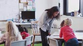 sınıf arkadaşı : Female infant school teacher leaning at desk helping school kids in a classroom