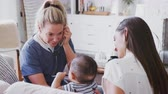 más : Female healthcare worker visiting young mum and her infant son at home, using stethoscope, close up