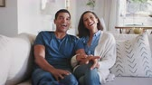 koleno : Young adult African American couple sitting in their living room watching TV together  laughing, close up