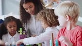 interessante : Female infant school teacher at table with three children using constructing blocks, selective focus Vídeos