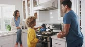 más : African American parents and their pre-teen daughter preparing food together in the kitchen