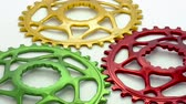 Colorful oval bicycle chainring gear rotating on a white background.