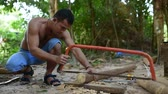 cambojano : Cambodian man prepares wood to build a traditional construction using handsaw. He incise wooden beam to fit with other wooden beam. 28 november 2017, Koh Rong Samloem. Cambodia.