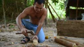 kamboçyalı : Cambodian man prepares wood to build a traditional construction using a tool like ax. He incise wooden beam to fit with other wooden beam. 28 november 2017, Koh Rong Samloem. Cambodia.