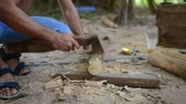 Камбоджа : Cambodian man prepares wood to build a traditional construction using a tool like ax. He incise wooden beam to fit with other wooden beam. 28 november 2017, Koh Rong Samloem. Cambodia.