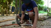 cambojano : Cambodian man prepares wood to build a traditional construction using a tool like ax. He incise wooden beam to fit with other wooden beam. 28 november 2017, Koh Rong Samloem. Cambodia.