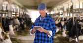 prezzi : Cow breeder checking on livestock and using digital tablet