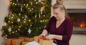 foco no primeiro plano : Young Woman Tying Ribbon On Christmas Present