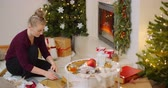 carta da pacco : Woman Wrapping Christmas Present By Fireplace At Home Filmati Stock