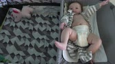 pack : Newborn baby in diapers on a changing table near a pack n play. Stock Footage