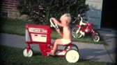 szemcsés : 8mm Vintage 1956 Boy Riding Toy Tractor. A retro 8mm reel-to-reel home movie film, professionally cleaned and captured in full 4k 3840x2160 UHD resolution plus post production including color correction, deinterlace, and deflicker.