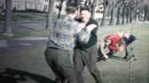 play video game : 1958 - Holiday Family Football Game Public Park Stock Footage