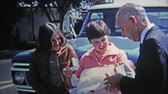 chrzest : 1969: Young mother has baby ready for baptism christening.