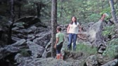 GREENSBORO, NC -1971: Girls playing around and hiking rocky boulder trail. Стоковые видеозаписи