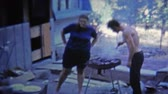 GREENSBORO, NC -1973: Man grilling food outside trailer house for wife and baby. Стоковые видеозаписи