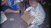 1958: Kid opens Christmas gift of army men in a box. Стоковые видеозаписи