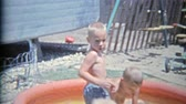 1963: Brother intimidating threatening with bucket of water in summer child pool.