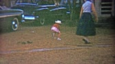 1959: Little dog running away from family trying to catch in front yard with classic car.