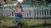 1957: Girl practicing Hawaiian style dance in backyard next to parked car.