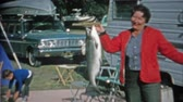 1966: Women catches big lake trout fish at trailer park campsite has trouble holding it.