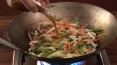 жареный : Sautéing chicken and vegetables in a wok, adding soy sauce Стоковые видеозаписи