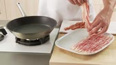 tiras : Rashers of bacon being placed in a pan