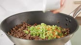 mão : Diced vegetables being added to minced meat