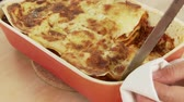 noodle dish : Lasagne being cut into pieces and removed from the dish Stock Footage
