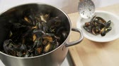 molusco : Cooked mussels being arranged on a deep plate