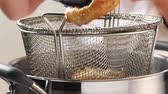 deepfry : Fried fish fillets being removed from a frying basket Stock Footage