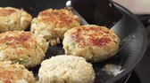 kotlety mielone : Crab cakes being fried in a pan