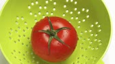 zoom out : A tomato in a colander