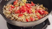 жареный : Rice being fried with diced aubergine and tomatoes