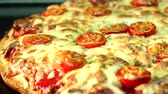 assar : A pizza topped with mozzarella and cherry tomatoes, baking in the oven (close-up) Vídeos