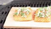 salmão : Marinated salmon pieces being grilled on a piece of cedar wood